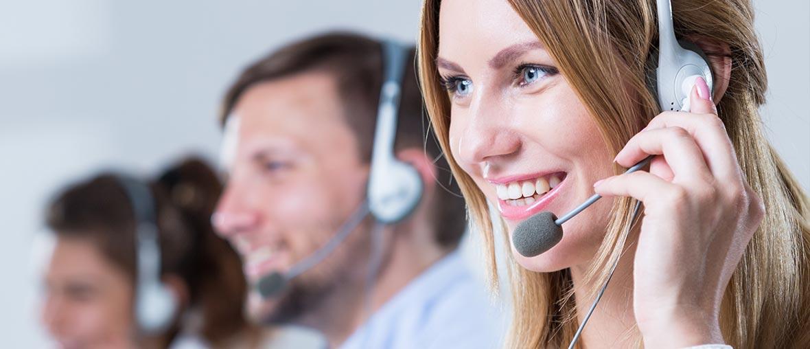 Junge Frau im Callcenter mit Headset. Im Hintergrund zwei Herren, ebenfalls im Callcenter tätig, leicht verschwommen.
