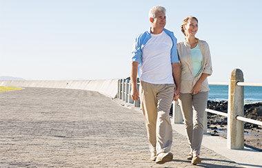 Älteres Paar läuft Hände haltend über eine Strandpromenade