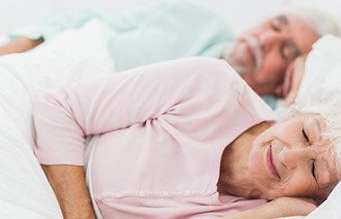 Altes Eherpaar liegt schlafend nebeneinander im Bett