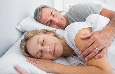 Älteres Ehepaar liegt schlafend nebeneinander im Bett