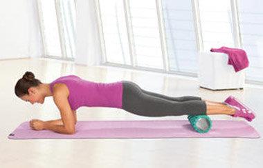 Eine Frau trainiert mit einer Faszienrolle auf einer Gymnastikmatte