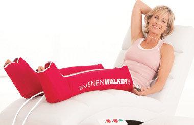 Frau im mittleren Alter liegt auf einem Liegestuhl und trägt den roten Venenwalker an den Beinen
