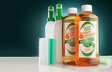 Zwei Flaschen Orangen Reiniger von Higloss neben Sprühflaschen und Putzschwämmen