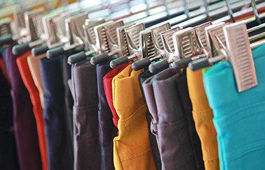 Mehrere Hosen auf Kleiderbügeln hintereinander auf Kleiderstange