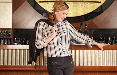 Model lehnt an einer Bar aus Holz. Sie trägt eine gestreifte Bluse, dunkle Hose und wirft sich ihre schwarze Jacke über die Schulter - alles von Monaco blue. Im Hintergrund ist die Bar mit Getränken bestückt.